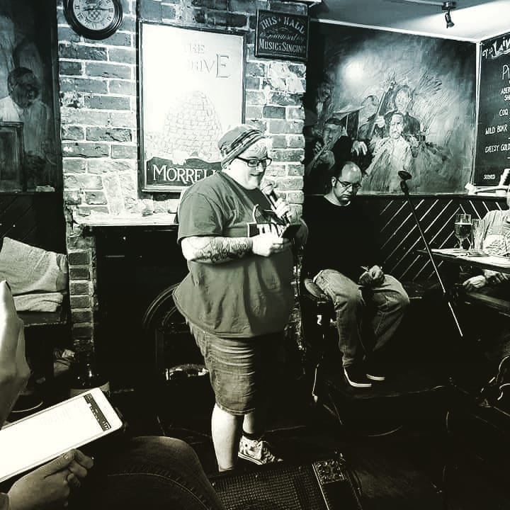 black and white image of a woman in a beanie, tshirt, denim shorts and converse speaking into a microphone in a pub