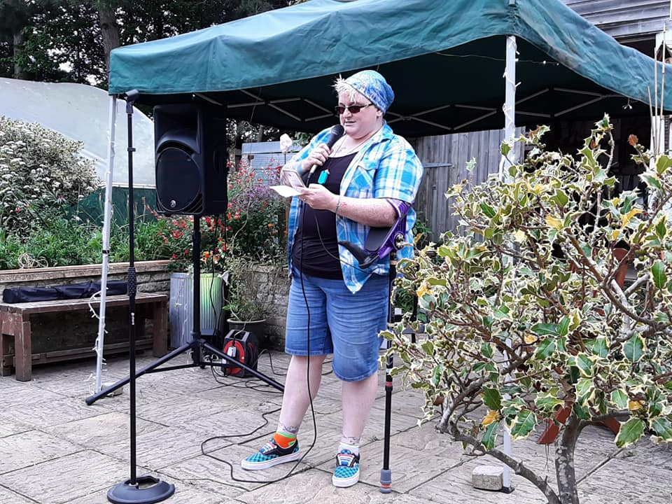 A photo of a woman in a blue beanie, black vest and blue shirt, denim shorts and checkerboard shoes, leaning on a purple crutch and speaking into a microphone. In the background is a green gazebo