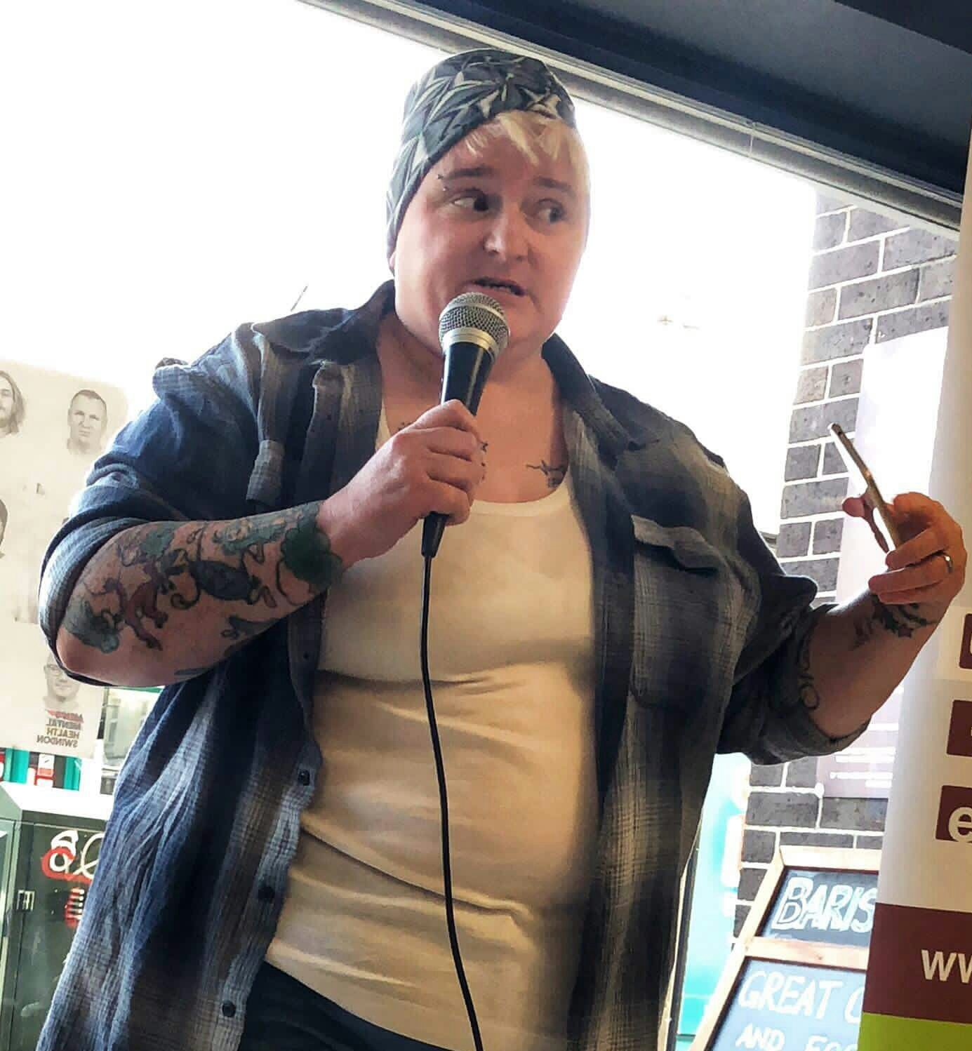Image of a woman with blond hair and a grey patterned beanie wearing a white vest and blue shirt, speaking into a microphone