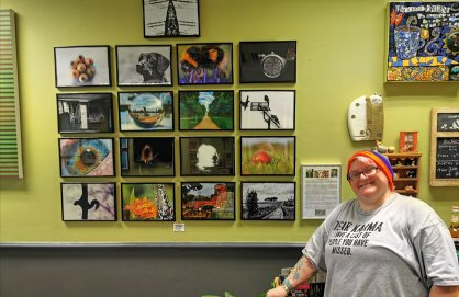 Wall of photographs. In front is a woman in glasses, a rainbow coloured beanie and a grey tshirt smiling for the camera