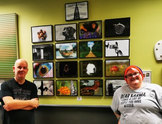 Wall of photographs. In front to the right is a woman in glasses, a rainbow coloured beanie and a grey tshirt smiling for the camera. To the left is a bald headed man in a black tshirt with folded arms