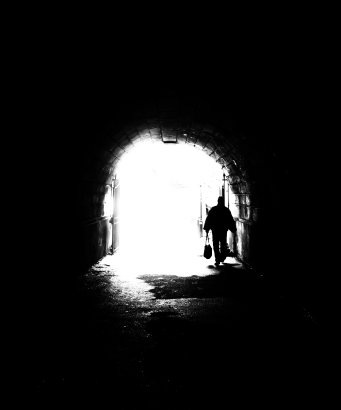 A silhouette of a person carrying a bag passing through a tunnel into a bright exit