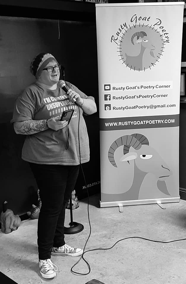 black and white image of a woman in a beanie, tshirt, jeans and converse speaking into a microphone. In the back ground is a banner reading Rusty Goat Poetry
