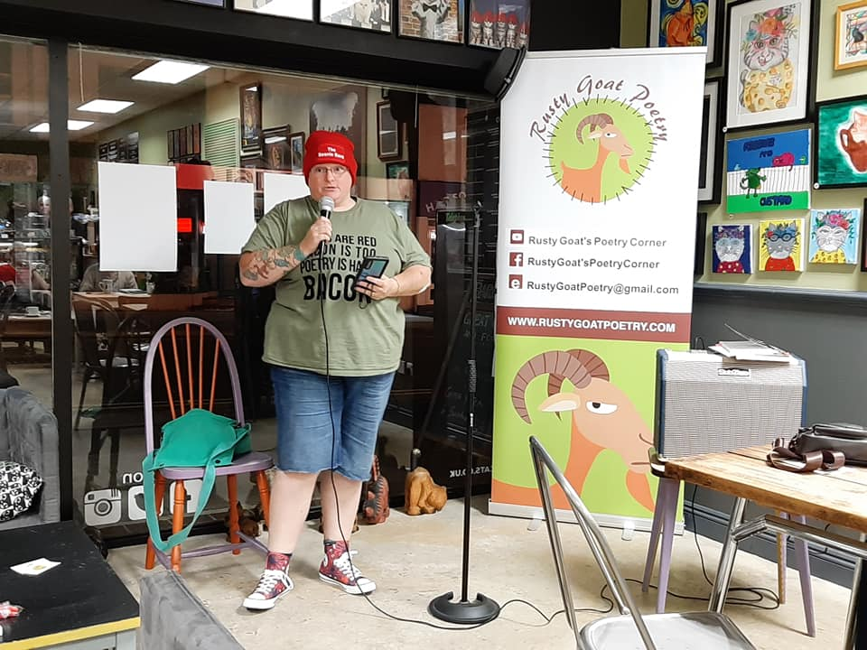 Image of a woman in a red beanie that reads The Beanie Bard, a khaki tshirt, denim shorts and converse speaking into a microphone. In the background is a banner reading Rusty Goat Poetry