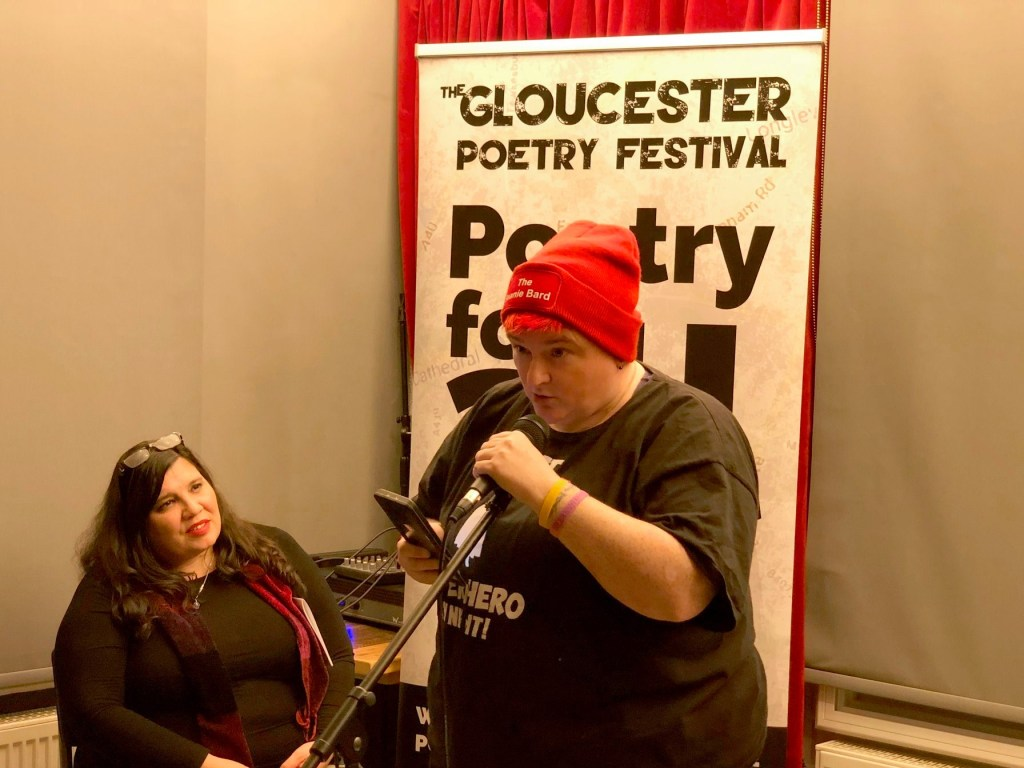 Image of a woman in a red beanie that reads The Beanie Bard and a black tshirt speaking into a microphone. In the background is a banner reading Gloucestershire Poetry Festival and a woman with black hair watching the performance