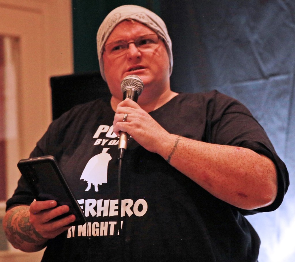Image of a woman in a grey beanie and black tshirt speaking into a microphone