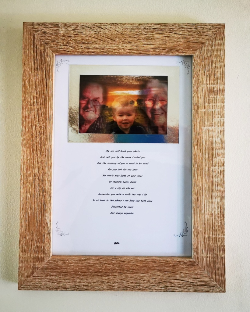 Image of picture frame. Picture in frame is of a young boy in the centre of 2 older people and underneath is a short verse
