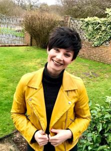 Image of a dark haired woman in a yellow jacket smiling at the camera in a walled garden