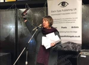 Image of a lady with bobbed dark grey hair in a scarf, cardigan and fingerless gloves speaking into a microphone and holding up a book