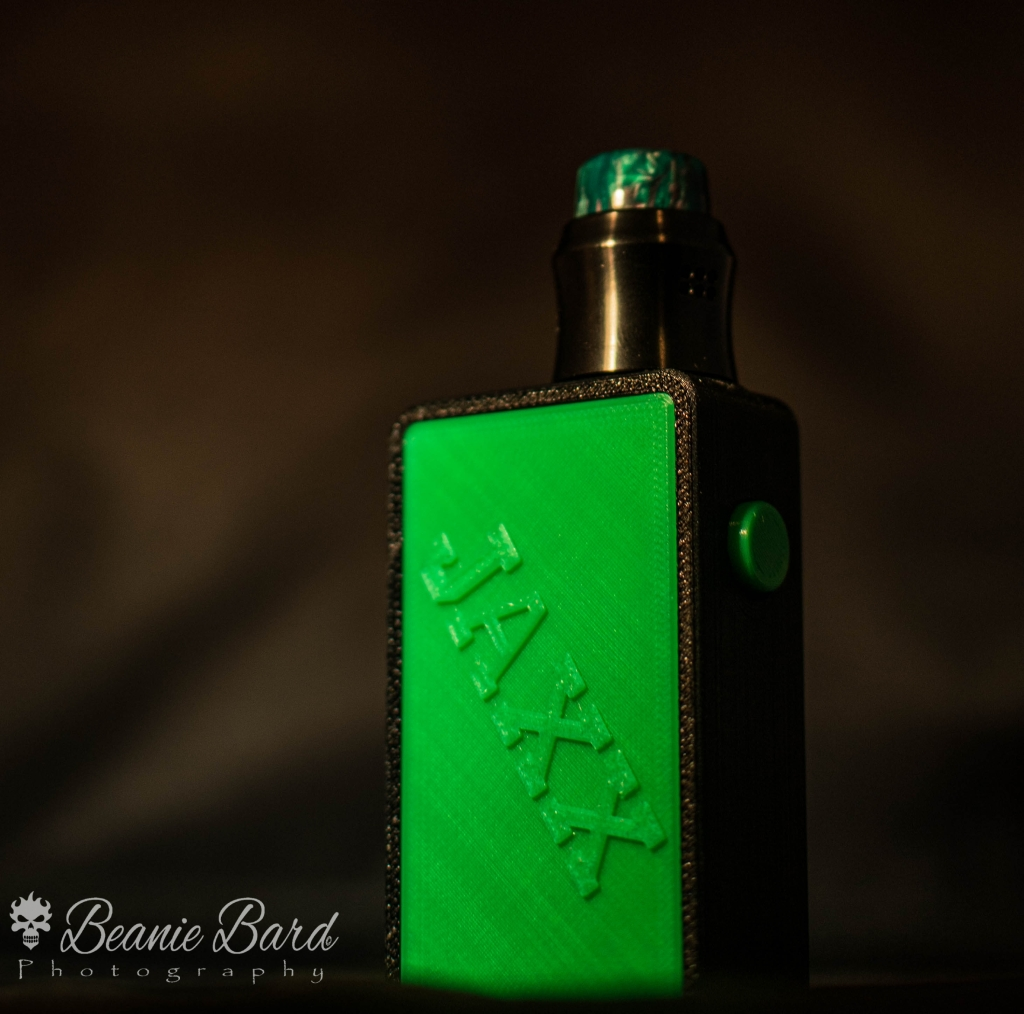Vape mod on a black background. Mod is green with the word Jaxx in raised lettering with a black tank and green mouthpiece