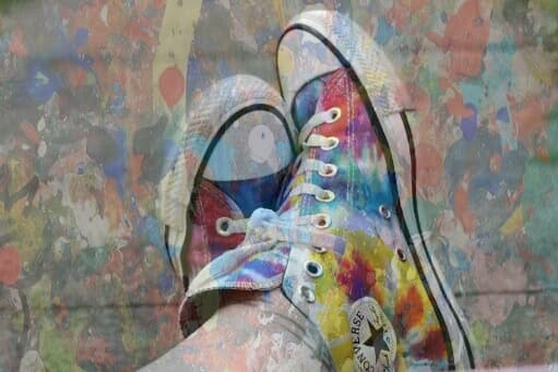 a pair of hightop shoes, with feet crossed, overlaid with a paint splatter effect