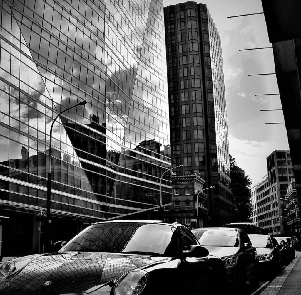 An image of high rise offices with highly reflective glass windows, upon which you can see the reflection of a cloudy sky. Parked next to the buildings are a row of shiny cars reflecting a lot of light off their windows also. Whole image is in black and white