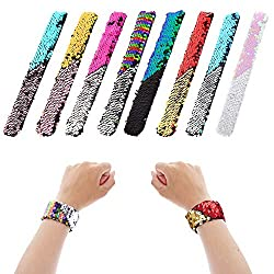 A picture of 6 slap bracelets covered in two sides sequins, and a pair of child's wrists modelling them
