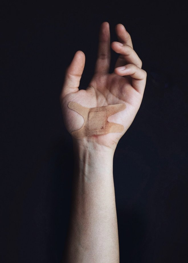 A hand against a black background with a bandaid on the palm