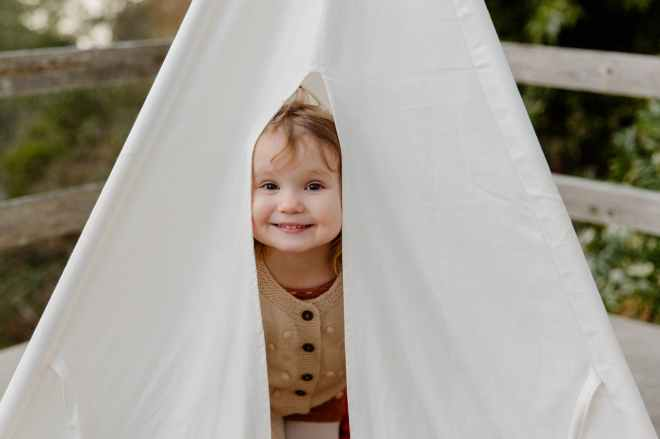 A small child peeking out from a playtent and smiling