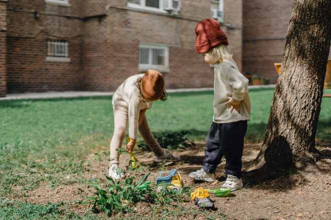 Two young children in beanie hats playing in the garden with spades and toy trucks