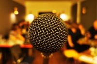 A close up view of the front of a microphone on a stand, the view of the room behind with people in it is very blurred