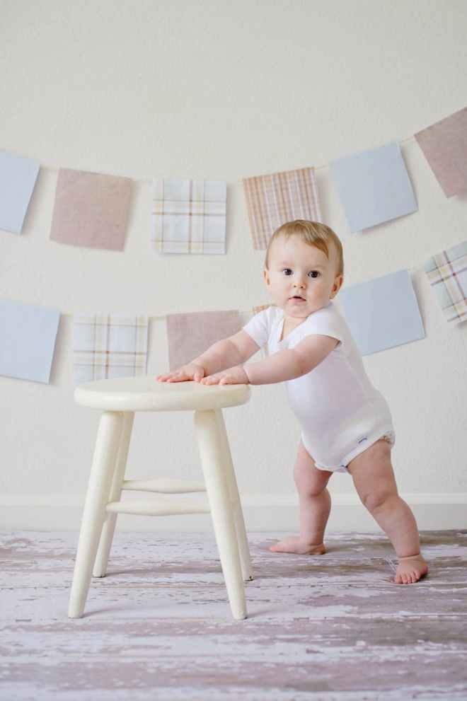 A photo of a baby in a vest stood up holding onto a stool with bunting in the background