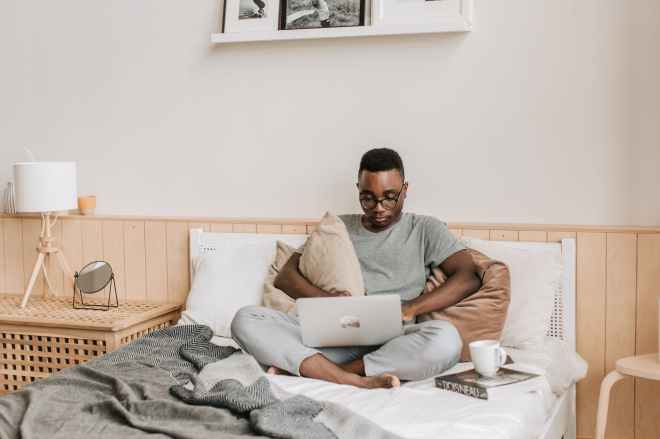 A man in glasses and grey pajamas sat crossed legged on his bed using a laptop with a book and cup of tea beside him