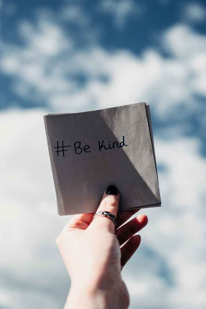 A hand wearing a thumb ring and black nail polish holding a folded piece of paper that reads #bekind against a blue sky